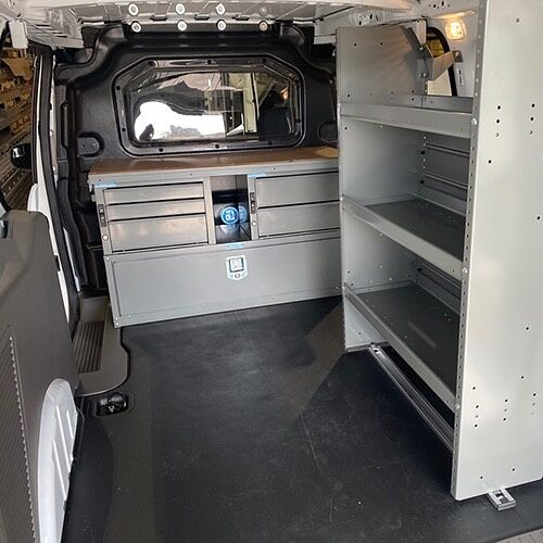 Composite bulkhead with a desk set up featuring a Thor power inverter underneath. Plus a passenger side shelving unit.  #bulkhead #vanupfit #workvan #telecommunications #thorpowerinverter